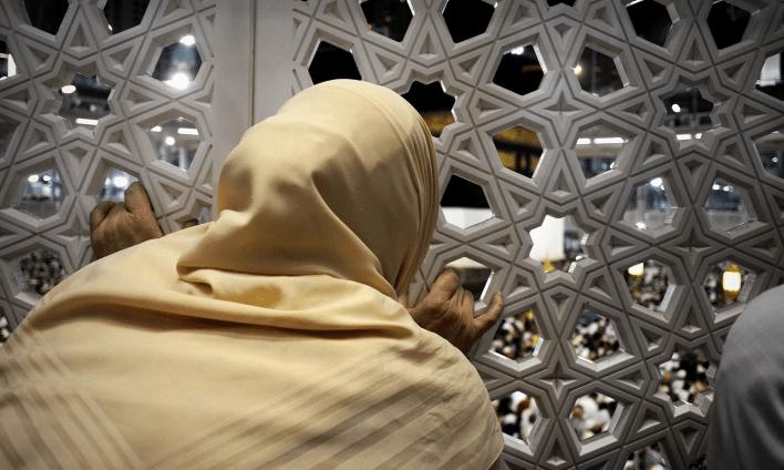 مسلم خاتون جالی سے خانہ کعبہ کو دیکھ رہی ہیں — فوٹو اے ایف پی