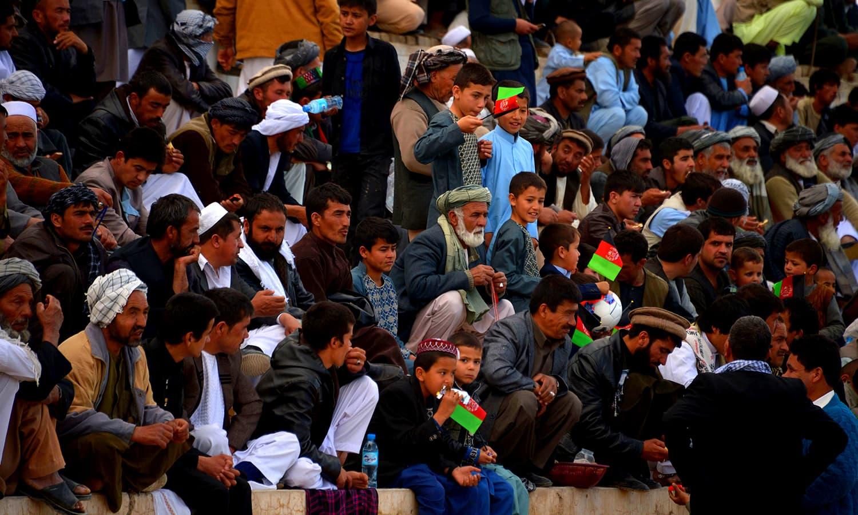 Spectators watch a game of buzkashi. ─ AFP