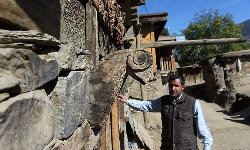 Kalash Peoples Development Newtwork (KPDN) activist Luke Rehmat stands at the door of a Kalash building of worship in Brun village in the Bumboret valley. — AFP