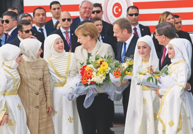 Nizip: German Chancellor Angela Merkel (centre) accompanied by EU Council President Donald Tusk (right) talks to young women at a refugee camp on Friday.—AP