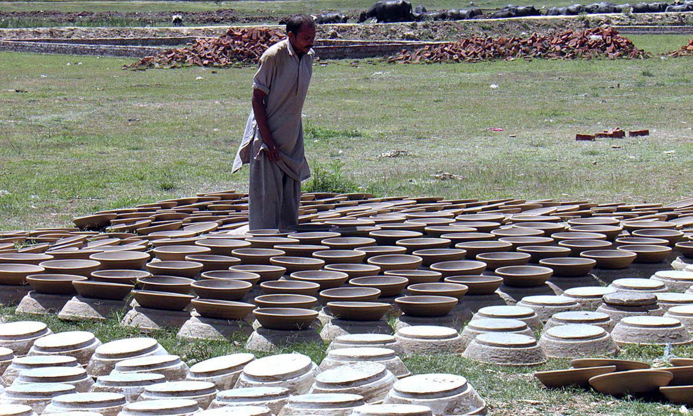 ایک مزدور سیالکوٹ میں مٹی سے اشیاء بنانے میں مصروف ہے — اے پی پی فوٹو