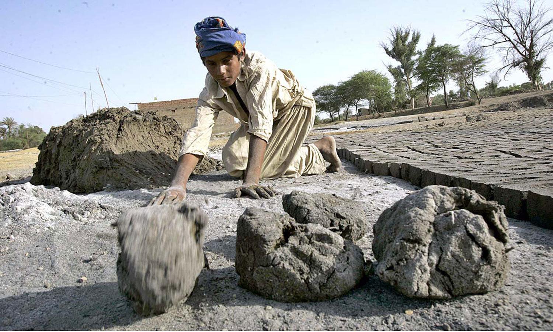 سندھ کے ضلع لاڑکانہ میں ایک مزدور اینٹیں بنانے کے لیے میٹریل تیار کرنے میں مصروف ہے — اے پی پی فوٹو