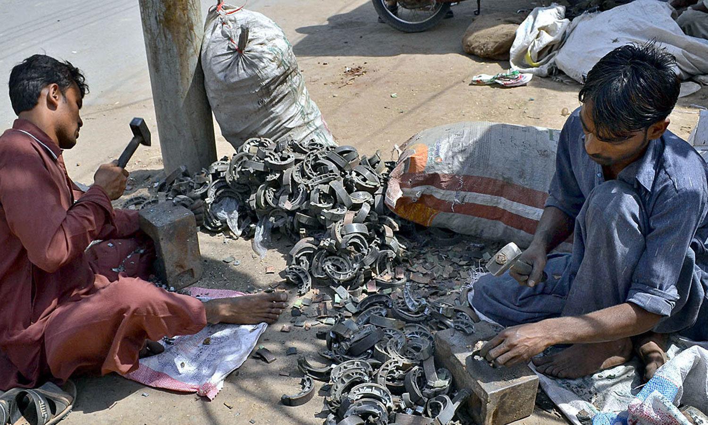ملتان کی اس تصویر میں کچھ مزدور موٹرسائیکل ڈسک بریک سے لیدر الگ کرنے کی کوشش کررہے ہیں — اے پی پی فوٹو