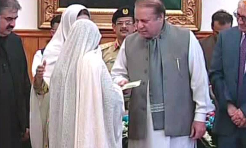 PM Nawaz handing out an NHP card. ─ DawnNews