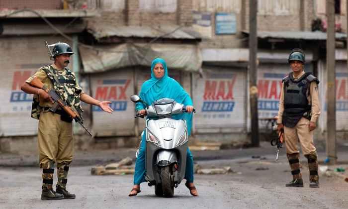 Indian paramilitary soldiers stop a Kashmiri woman during curfew in Srinagar. —AP