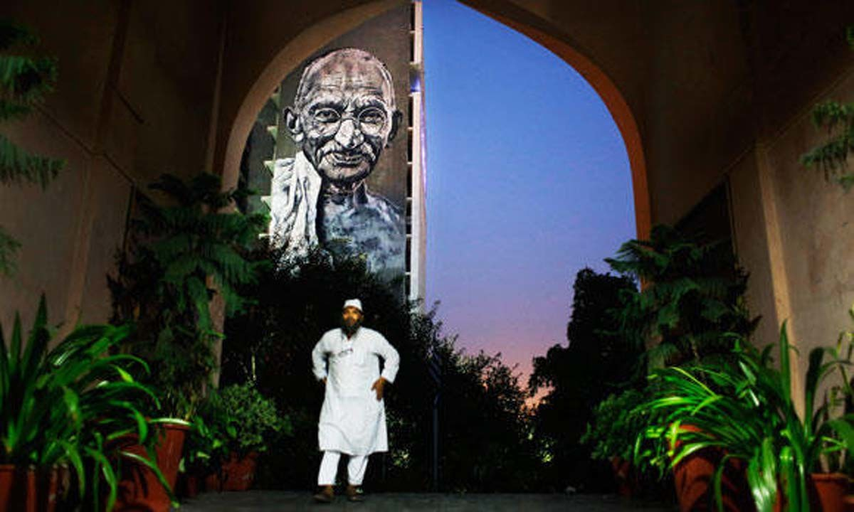 An Indian Muslim man walks into a mosque in New Delhi. A portrait of Mahatma Gandhi hangs on the wall of the  Delhi Police Headquarters in the background | AP