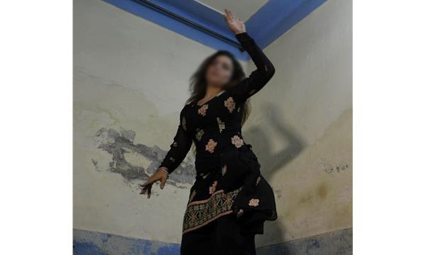 A prostitute from the red light district practising her final dance steps before going out for an event in Lahore ─ AFP