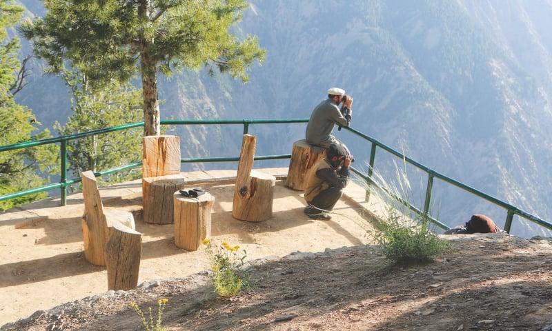 A man looking through binoculars at the lookout point at the Chitral Gol National Park.