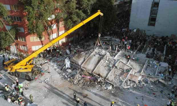 Rescuers look for survivors in a multi-storey building flattened by a powerful quake in Mexico City. —AFP