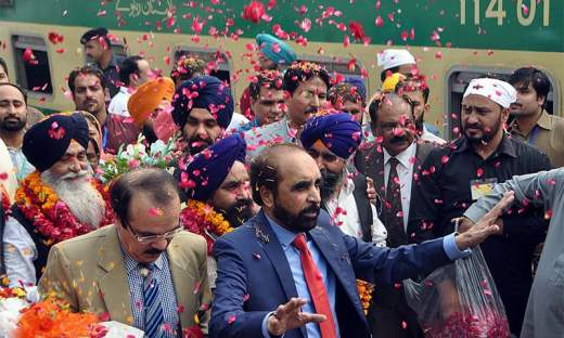 Sikh devotees are showered with rose petals upon their arrival at Wagah border. — APP