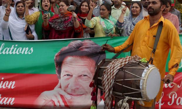 عمران خان کے وزیر اعظم کا عہدہ سنبھالنے پر پی ٹی آئی کارکنان نے ڈھول کی تھاپ پر رقص کیا اور مٹھائیاں تقسیم کیں — فوٹو: اے پی