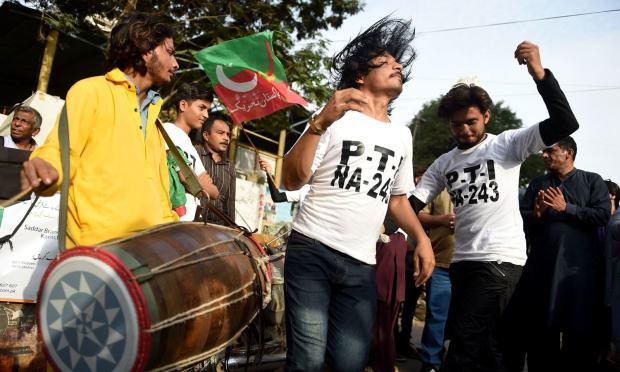 عمران خان کے وزیر اعظم کا عہدہ سنبھالنے پر پی ٹی آئی کارکنان نے ڈھول کی تھاپ پر رقص کیا اور مٹھائیاں تقسیم کیں — فوٹو: اے ایف پی