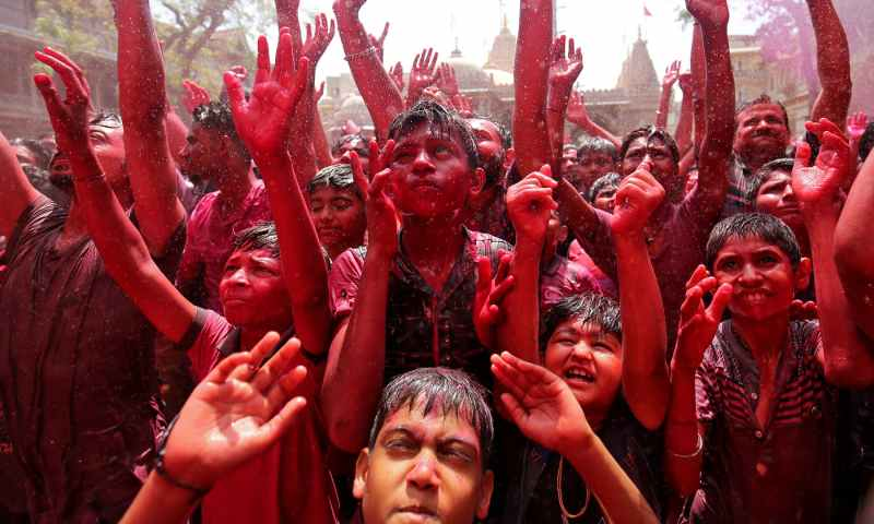 Hindu devotees raise their hands daubed in colours as they pray on a temple premises during Holi celebrations in Ahmedabad, India. — Reuters