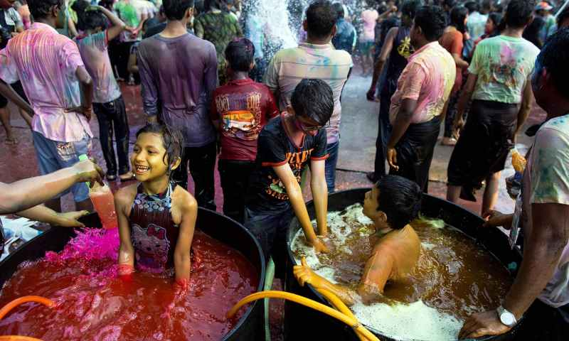 Myanmar's Hindu children soak in a pool of coloured water as they celebrate the Holi festival in Yangon on March 20, 2019. — AFP
