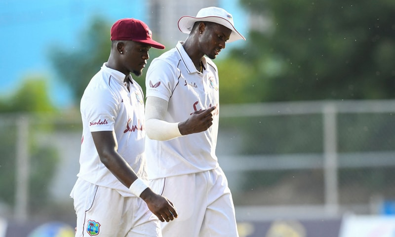 Jayden Seales (L) and Jason Holder (R) of West Indies walk off the field during day one of the first Test between West Indies and Pakistan at Sabina Park in Kingston, Jamaica. — AFP