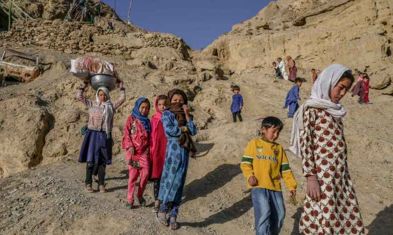 Children walk to a river from their village near the cliffs pockmarked by caves where people still live as they did centuries ago in Bamiyan, Afghanistan on October 3, 2021. — AFP