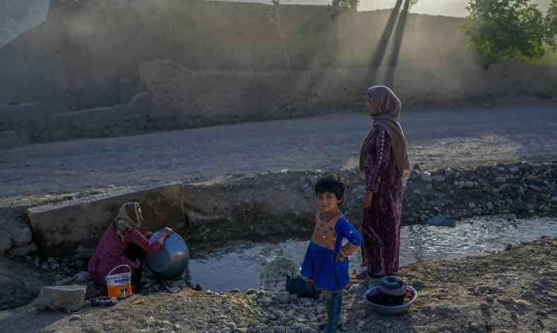 A Hazara ethnic woman (L) washes dishes in front of a village in Bamiyan, Afghanistan on October 3, 2021. — AFP