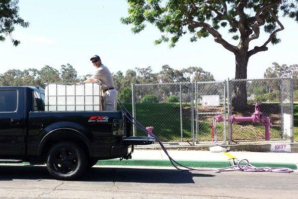 圖:2016年7月30日,聖地亞哥市供水區首次為居民客戶提供免費循環水(Recycled Water),用以清洗庭院、澆灌植物、洗車等,但不能做為飲用水。圖為一名居民將從紫色水管流出的循環水裝入卡車上的巨大容器。(聖地亞哥市公共事業部提供)