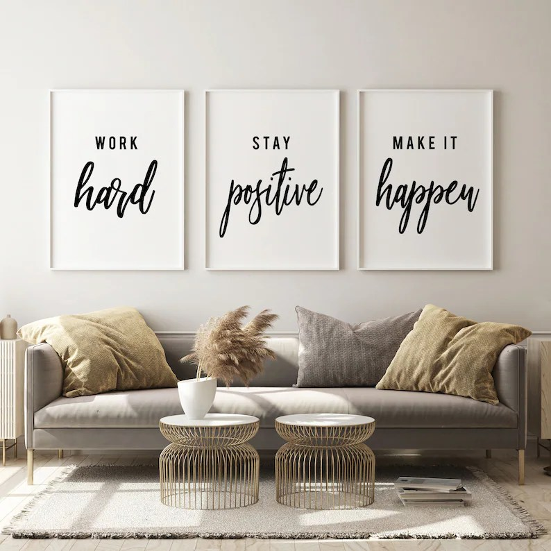 """Photo of Modern home office ideas on etsy, including three framed prints with white background and black writing. Room has a light grey couch with pillows, a rug and two small round tables in front of the couch with a white vase on top of one of them with brown feathery plant in it. Prints say """"Work hard"""", """"Stay positive"""", and """"Make it happen""""."""