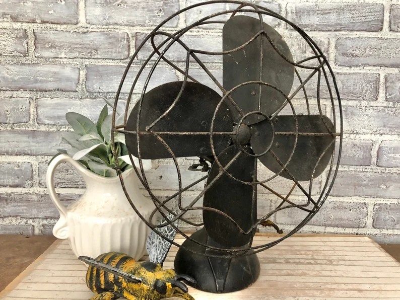Photo of Industrial home office ideas on etsy. Photo depicts a rustic-looking black fan sitting on a wooden table along with a beige pitcher vase filled with a green plant, and a small statue of a yellow and black bee. Grey brick background.