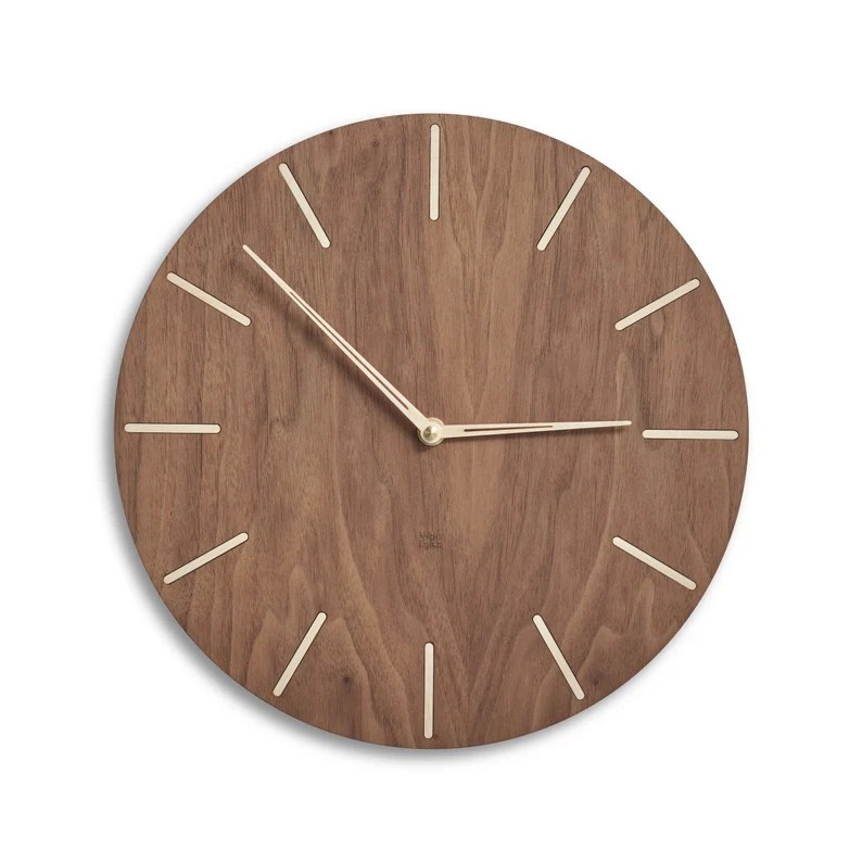 Photo of a wooden clock mounted to a white wall. No numbers appear on the clock, instead there are lines in each time slot and two metal clock hands.