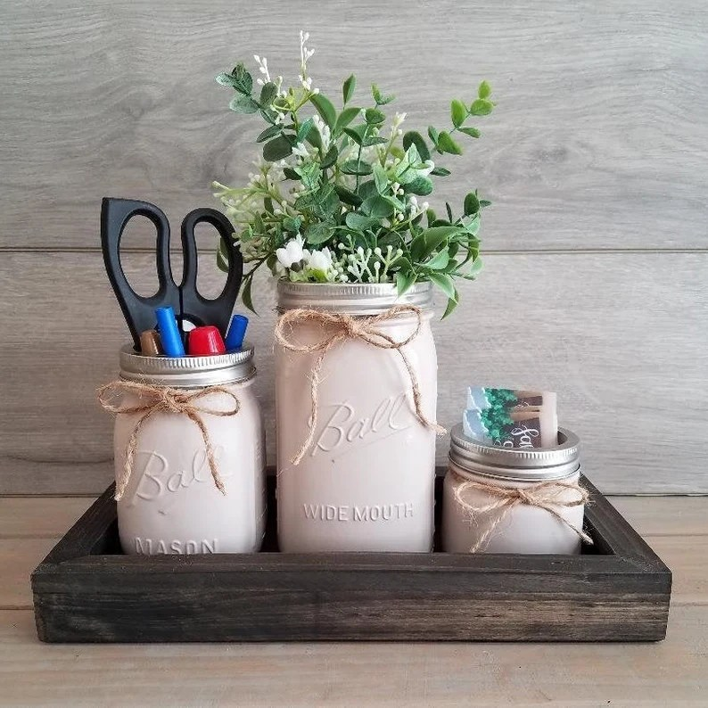 Photo of beige painted Ball brand glass jars with twine bows tied onto the tops. Jars have items inside including scissors, pens, markers, business cards and some green and white plants. Jars are sitting in a wooden tray on a wooden surface with a wooden background.