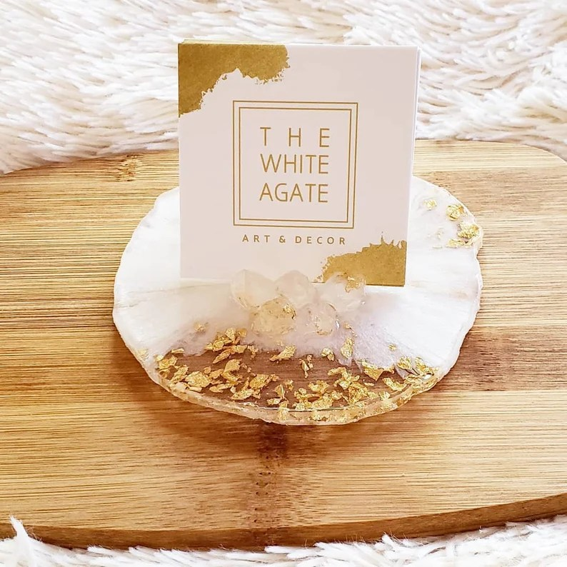 """Photo of a business card sitting in a white rock marble looking card holder with gold-looking flakes imbedded into it. The card holder is sitting on a wooden board which is sitting on a white carpet. Card says """"The White Agate Art & Decor""""."""
