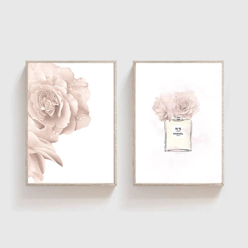 Photo of Glam home office ideas on etsy, including two framed images that depict a perfume bottle and pink roses. Framed images are hung on a wall that is white.