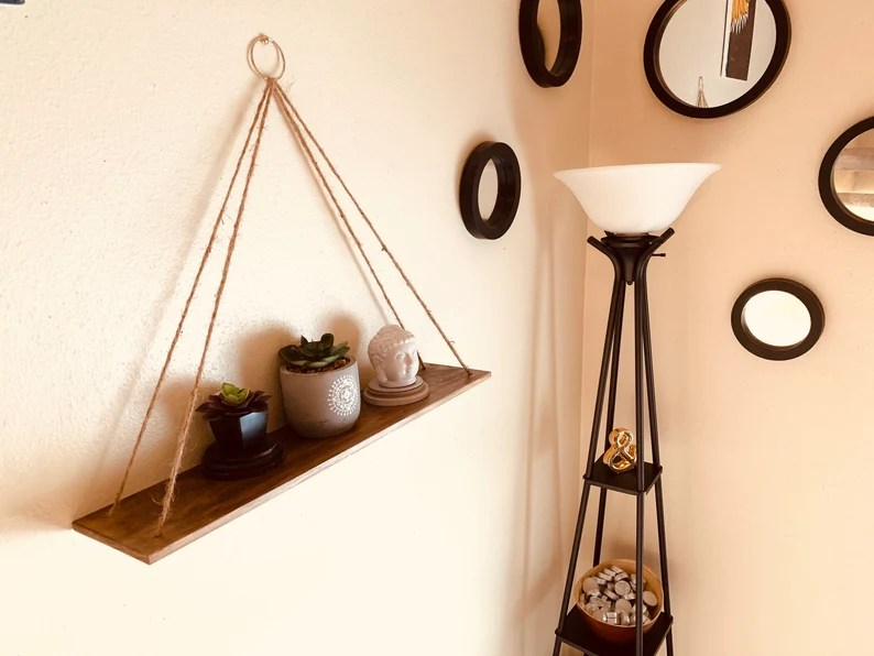Photo of a hanging shelf made from wood and twine with two potted succulents on top and a small statue of Buddha's head. Wall is cream colored and has five small round mirrors with black frames on it. There is also a black metal frame floor lamp with a white lampshade and two shelves in the lamp with home decor items on it.