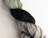 Hand dyed 75/25% superwash merino/nylon sock fingering 4ply weight yarn.  Snape - variegated grey and black sock yarn with green speckles.