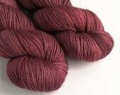 Hand dyed MCS 4ply/fingering weight yarn, Superwash merino/cashmere/silk yarn in semi-solid berry red-purple. Tonal dark red luxury yarn.