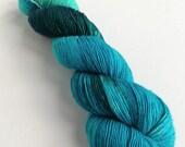 Hand dyed yarn, singles superwash merino 4ply wool yarn, variegated turquoise blue, teal, black fingering weight, knitting, crochet yarn.