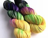 Hand dyed yarn. indie dyed superwash merino aran weight yarn, variegated yellow, green, black, purple and blue.  Cat People, horror inspired