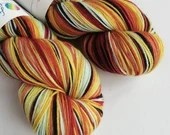 Hand dyed sock yarn, variegated superwash merino/nylon sock fingering 4ply weight yarn.  Indie dyed sock yarn, red orange yellow brown yarn.