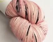 Indie dyed superwash merino/nylon/stellina sparkle sock yarn.  Hand dyed variegated peachy-pink yarn with black speckles.