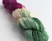 Hand dyed baby alpaca chunky yarn. Bulky weight yarn in Luna variegated colourway with green, plum and speckles.