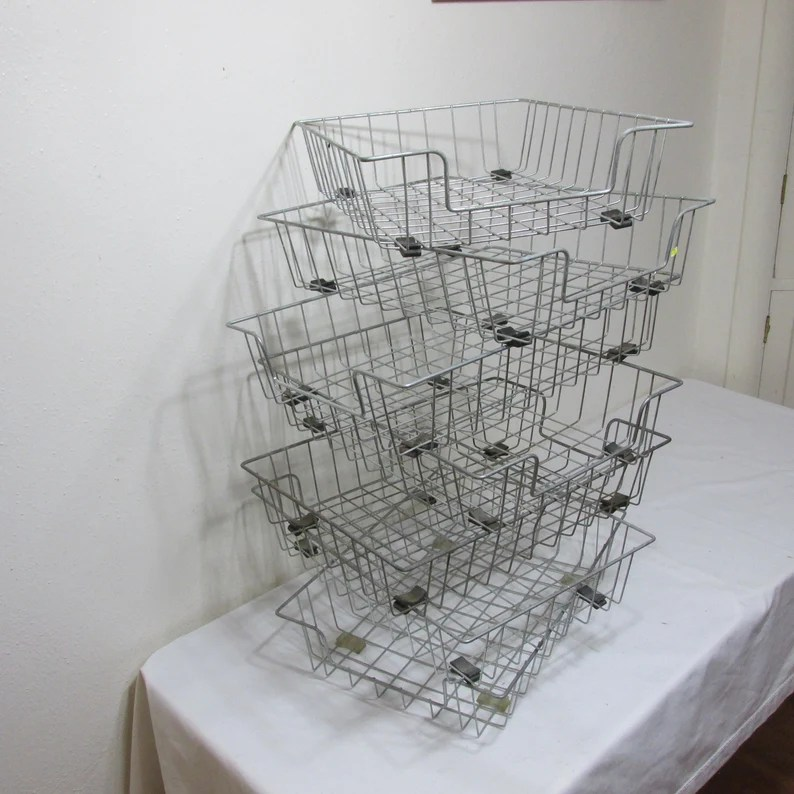 Photo of metal baskets stacked on a table covered in a white tablecloth. Wall in background is white.