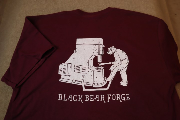Bear working with power hammer. Black Bear Forge Tee shirt
