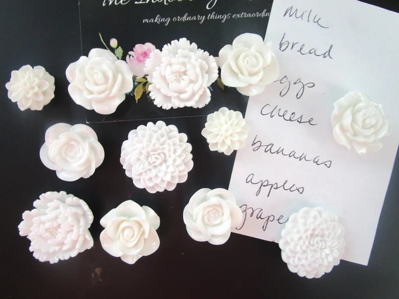 Photo of white floral designed magnets affixed to a black board with a black and floral invitation and a handwritten shopping list on white paper.