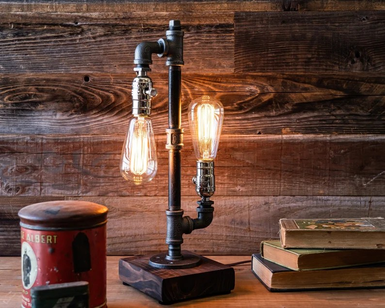 Photo of antique-looking lightbulbs in an antique-looking lamp sitting in front of a wooden wall. Three books are stacked next to the lamp, and a old-looking tin can with lid is also next to the lamp.