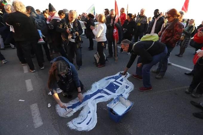 Des manifestants affichent leur soutien aux migrants en peignant sur le sol des silhouettes de migrants décédés, samedi 16 décembre, à Menton.
