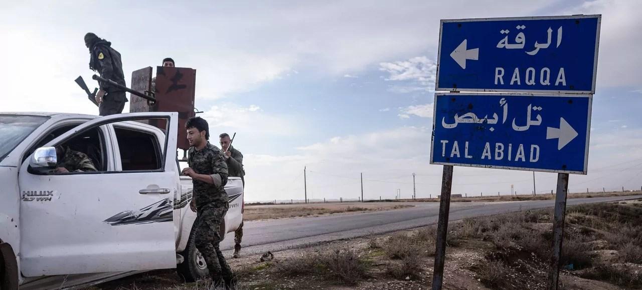 Sur leur pick-up munis d'une mitrailleuse lourde, des combattants kurdes de l'YPG ont pris position sur la route de Raqqa.