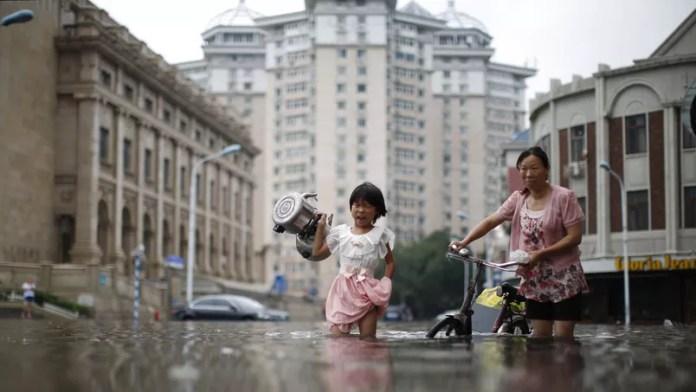 À Tianjin, une petite fille et sa mère tentent d'emporter avec elles quelques affaires avant de fuir la ville totalement inondée. Au total près de 1,6 millions de personnes ont dû être évacuées.