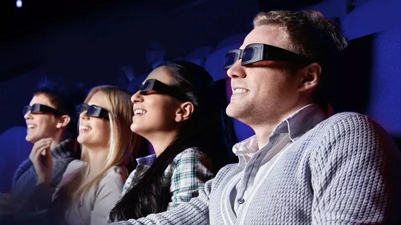 Des spectateurs devant un écran panoramique, équipés des lunettes 3D.