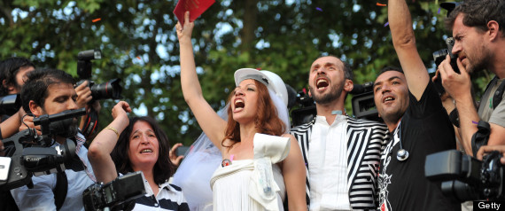 Newly married couple Nuray (L) and Ozgur chant slogans in Gezi Park on July 20, 2013 in Istanbul after being married at the Sisli district's municipal building. (OZAN KOSE/AFP/Getty Images)