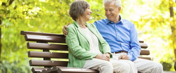 older people talking on park bench
