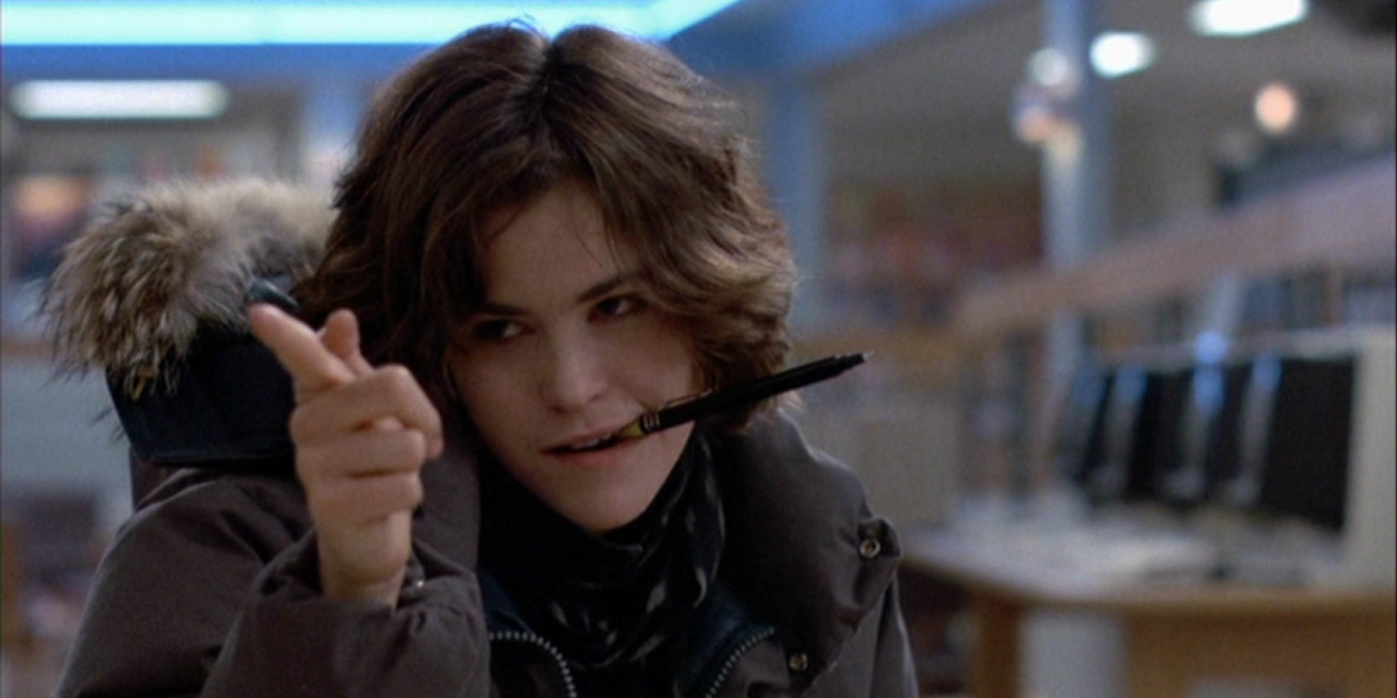 Ally Sheedy in The Breakfast Club (1985). Allison, wearing a big grey puffer coat with a fluffy hood, is sitting in the school library in detention. She has a black pen stuck in her mouth, and is doing snarky finger guns/pointing.