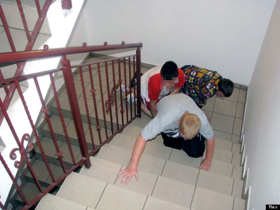Salesian schoolchildren climbing stairs using hands and knees
