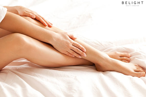 Close-up-of-a-perfect-female-legs-Woman-applying-moisturizer