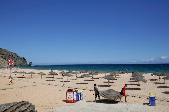 Two men set up sun umbrellas at the beach in Praia da Luz, in Portugal's Algarve coast, Thursday, June 4, 2020. (Photo: AP)